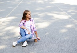 Smiling cute little girl child sitting with a skateboard. Preteen with penny board outdoors in summer day