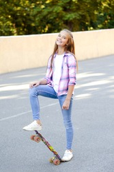 Smiling cute little girl child standing with a skateboard. Preteen with penny board outdoors in summer day