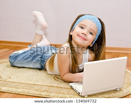 Smiling cute little girl with a laptop at home on the floor
