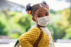 Smiling cute little girl with school backpack and protective face mask ready for first day of school during covid pandemic. Black kid going back to school during coronavirus pandemic disease.