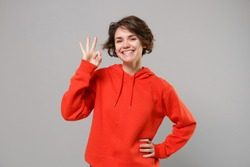 Smiling cute young brunette woman girl in casual red hoodie posing isolated on grey wall background studio portrait. People sincere emotions lifestyle concept. Mock up copy space. Showing OK gesture