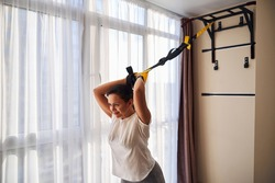 Smiling cute young Caucasian female athlete performing the overhead triceps extension with the suspension trainer