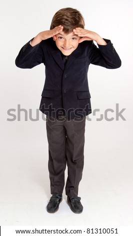 Smiling cute young schoolboy in vest and tie trying to see something