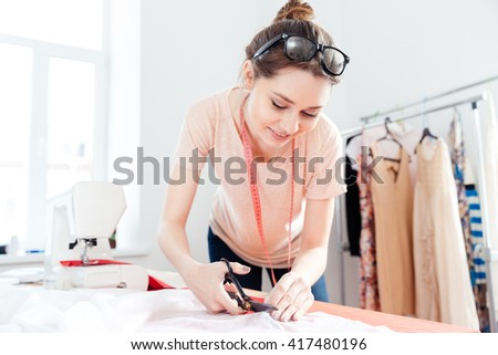 Smiling cute young woman seamstress standing and cutting white fabric with scissors