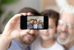 Smiling dad, little son and grandfather sit on couch make self-portrait picture on smartphone, happy three generations of men posing for selfie taking on cellphone enjoy spending time together at home