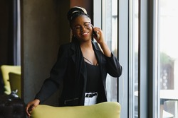 Smiling dark skinned woman in trendy wear laving cafe talking on mobile phone via roaming tariffs,african american millennial female walking and making smartphone call satisfied with connection