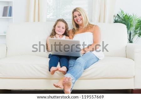 Smiling daughter and mother relaxing on the sofa with notebook while they are looking into the camera