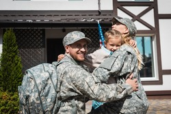 Smiling daughter hugging father and mother in military uniforms near house with american flag