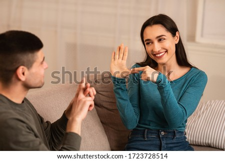 Smiling deaf and mute couple communicating at home using sign language, sitting on couch in living room Stockfoto ©