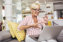 Smiling deaf senior woman talking using sign language on the laptop