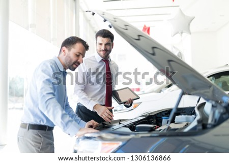 Smiling dealer holding digital tablet while looking at client analyzing car engine