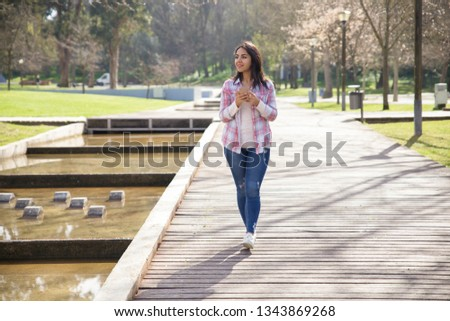Smiling delighted girl enjoying landscape in city park. Young woman in checked shirt and jeans using smartphone and walking outdoors. Walking outdoors concept