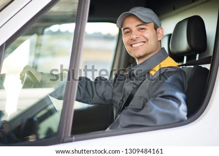 Smiling deliverer driving van