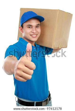 smiling delivery man in blue uniform carrying packages while gesturing thumb up sign isolated on white background