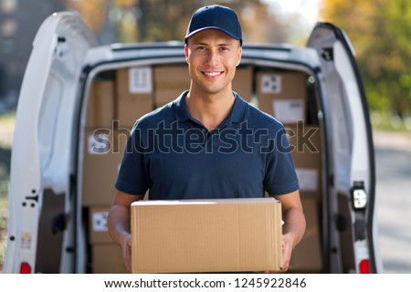 Smiling delivery man standing in front of his van #1245922846