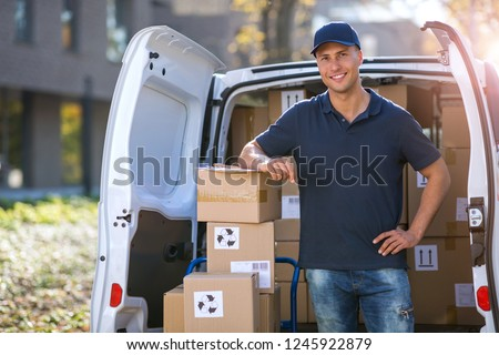 Smiling delivery man standing in front of his van
