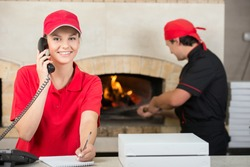 Smiling delivery woman of pizza on the phone and chef baker with long handled bread pan baking pizza into wood fire oven done.