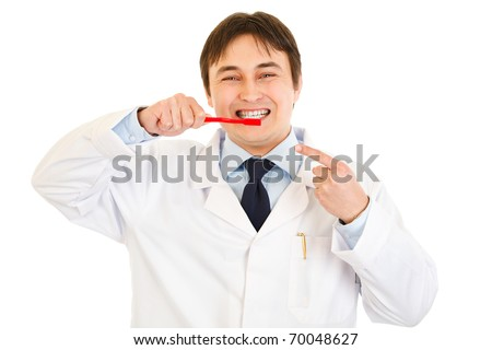 Smiling dentist pointing finger on toothbrush  isolated on white. Concept - healthy teeth