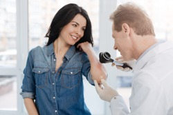 Smiling dermatologist enjoying appointment with patient in the hospital