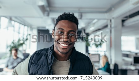 Smiling designer standing in workplace and looking at camera. Handsome young man in design office.