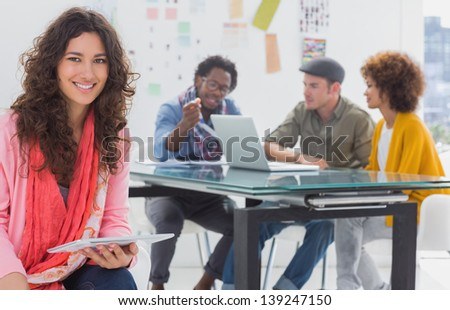 Smiling designer using tablet with team at work behind her