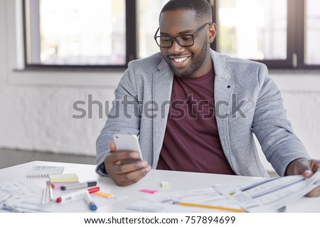 Smiling director of corporation wears formal clothes, uses smart phone for banking online, checks notification. Prosperous businessman satisfied with financial news reads on web page, uses internet #757894699