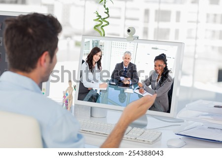 Smiling director sitting at the desk in front of the window between two employees against designer having a video chat