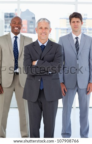 Smiling director standing in front of a relaxed executive and a serious employee