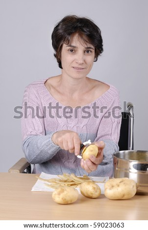 Smiling Disabled adult woman in wheelchair peeling potatoes