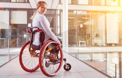 Smiling disabled businesswoman in wheelchair in office as inclusion concept
