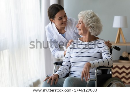 Smiling disabled elderly woman sitting in wheelchair talking with caring young nurse in living room, older generation receive homecare physical and moral support, caregiving and rehabilitation concept ストックフォト ©