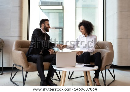 Smiling diverse business partners shaking hands at meeting, greeting, African American businesswoman and Caucasian businessman handshaking, making agreement, successful job interview or negotiations