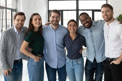Smiling diverse business people, successful team, staff members hugging, standing in modern office, looking at camera, happy overjoyed employees colleagues posing for corporate photo