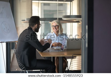 Smiling diverse businesspeople have fun talking discussing business ideas at meeting in office, happy man and woman employees or partners speak chat cooperating at company briefing in boardroom