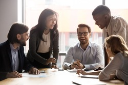 Smiling diverse businesspeople sit at office desk talk laugh discussing business ideas together, happy multiracial colleagues brainstorm joke negotiate at briefing in boardroom, cooperation concept