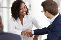 Smiling diverse businesswoman and businessman shake hands make partnership deal agreement at group office meeting negotiation thank for good teamwork expressing respect gender racial equality concept