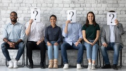 Smiling diverse candidates applicants sitting in row with unknown people holding paper sheets with question marks, successful hired man and women getting job, employment and recruitment concept