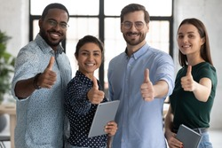 Smiling diverse employees team showing thumbs up, looking at camera, happy overjoyed colleagues recommending best corporate service, good career, human resources and employment concept