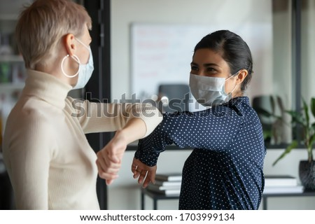 Smiling diverse female colleagues wearing protective face masks greeting bumping elbows at workplace, woman coworkers in facial covers protect from COVID-19 coronavirus in office, healthcare concept