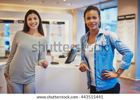 Smiling diverse girl friends wearing striped blouse and blue jean shirt stand against counter in optical shop #443515441