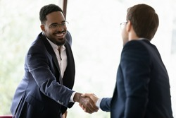 Smiling diverse male business partners shake hands get acquainted greeting at office meeting, happy multiracial man colleagues handshake close deal after successful negotiation, partnership concept