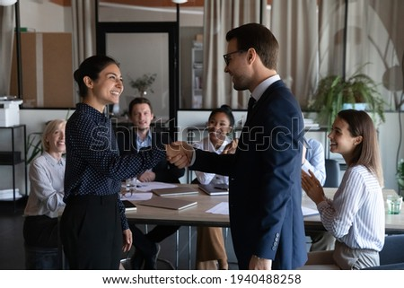 Smiling diverse multiracial employees handshake close deal agreement at meeting. Happy multiethnic businesspeople shake hand get acquainted greet at briefing, congratulate colleague with promotion. Foto stock ©