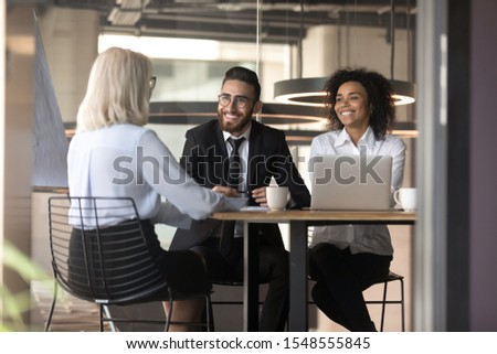 Smiling diverse multiracial employers have fun talking with female job applicant at interview, happy multiethnic recruiters or headhunters laugh speaking with woman candidate make good impression