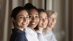 Smiling diverse multiracial female employees workers show team unity and leadership at workplace. Happy multiethnic women colleagues coworkers feel motivated in office. Success, recruitment concept.