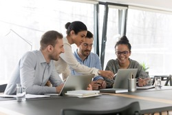 Smiling diverse young colleagues gather at desk in office look at laptop screen brainstorming at meeting together, happy multiracial employees cooperate using computer at briefing, teamwork concept
