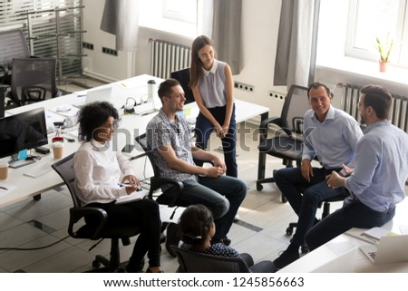 Smiling diversity team of employees, interns sitting circle, listening to business coach on training, trainer, discussing business strategy, plan with male leader, involved in team building activity
