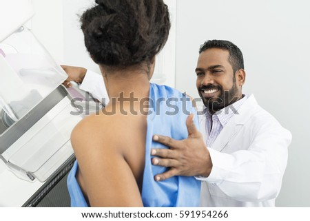 Smiling Doctor Assisting Patient Undergoing Mammogram X-ray Test