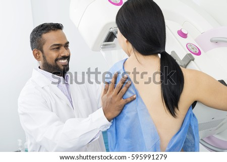 Smiling Doctor Assisting Woman Undergoing Mammogram X-ray Test