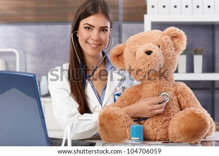 Smiling doctor examining teddy bear with stethoscope.