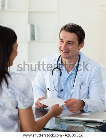 Smiling doctor giving a prescription to his female patient during a visit